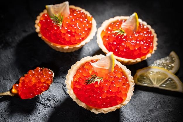 Тарталетки с красной икрой на черном столе. изысканные морепродукты