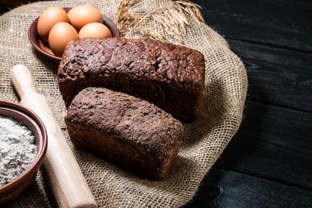 Смешанный хлеб на темном каменном столе. вид сверху с копией пространства