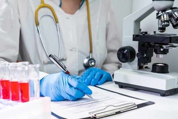Врач записывает результаты анализа крови на бланке. рабочее место врача - микроскоп, пробирки с кровью