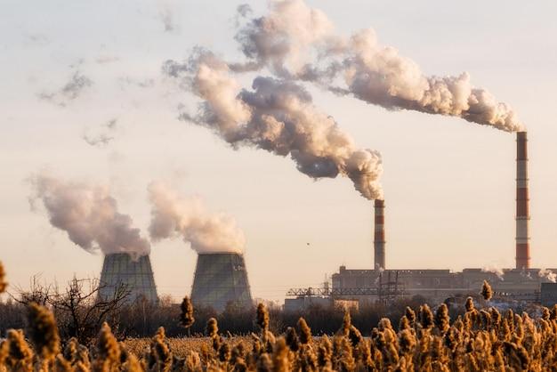 工場はパイプから汚れた煙を放出します