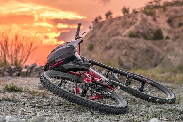 日没の黒いフルフェイスヘルメットとダウンヒルバイクのバックショット。