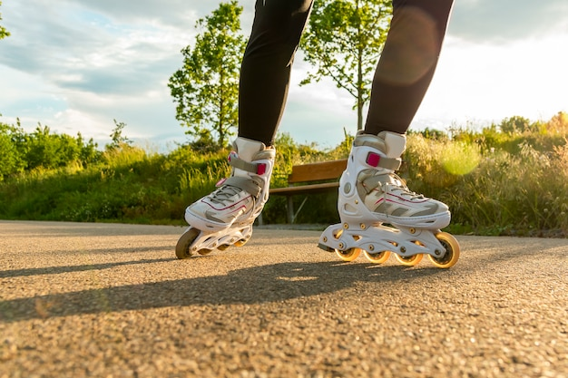 Крупным планом белых роликовых коньков на пути. ноги женщины с лезвиями ролика на солнечном дне.