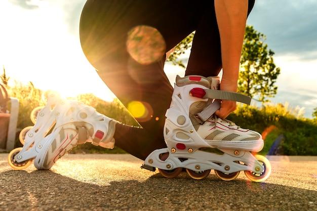 Женщина подтягивает роликовые коньки на дорожке. ноги женщины с лезвиями ролика на солнечном дне.