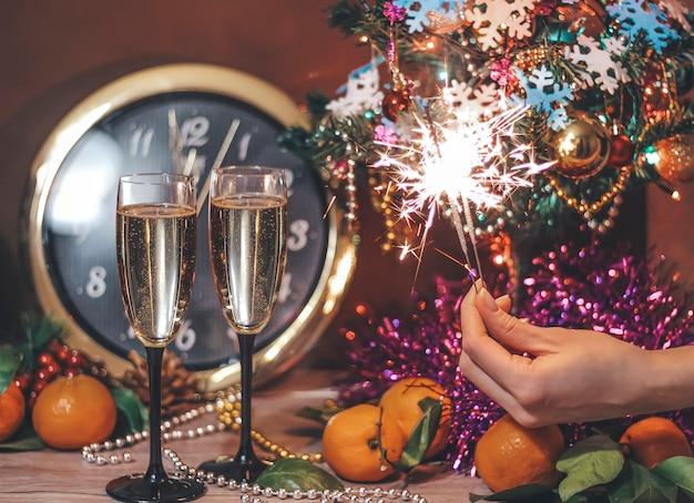 シャンパンと女性の手に花火のグラスでクリスマス組成
