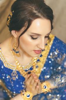Индийская женщина косплей. молодая красивая женщина в голубом индийском платье сари крупным планом на разноцветном коричневом фоне