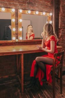 赤いロングドレスの若いセクシーな女性は、撮影の準備をし、楽屋の鏡で彼女の反射を見て