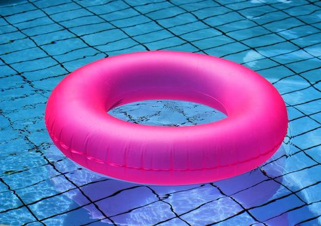Розовый надувной круг крупным планом на поверхности бассейна