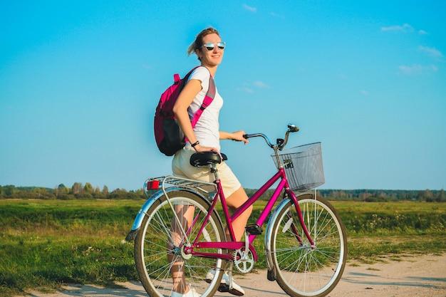 緑の野原の背景に夏に彼女のピンクの自転車のクローズアップで立っている若い美しい女性
