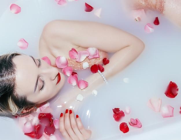 Молодая сексуальная девушка принимает ванну с лепестками роз