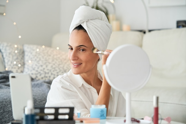 Женщина носит макияж в гостиной своего дома со всем необходимым для макияжа, как профессионал.