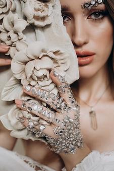 彼女の手で粘土の彫刻を持つ女性