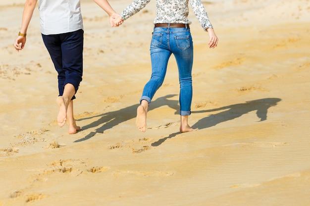 Влюбленная пара босиком бежит по песчаному пляжу