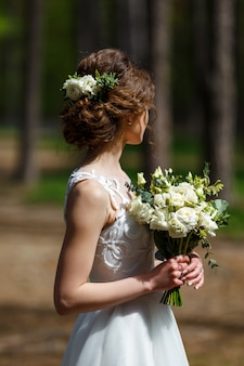 Невеста с белыми живыми цветами в волосах и свадебный букет в лесу