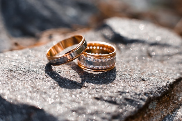 Золотые обручальные кольца с множеством драгоценных камней, лежащие на сером камне