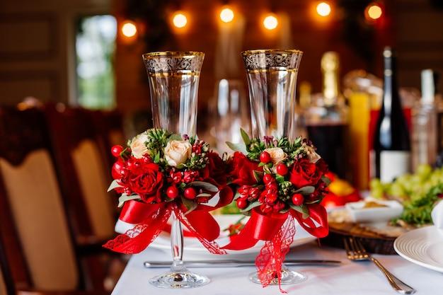 Два пустых свадебных бокала, украшенные зеленью, красными розами и лентой, стоят на банкетном столе