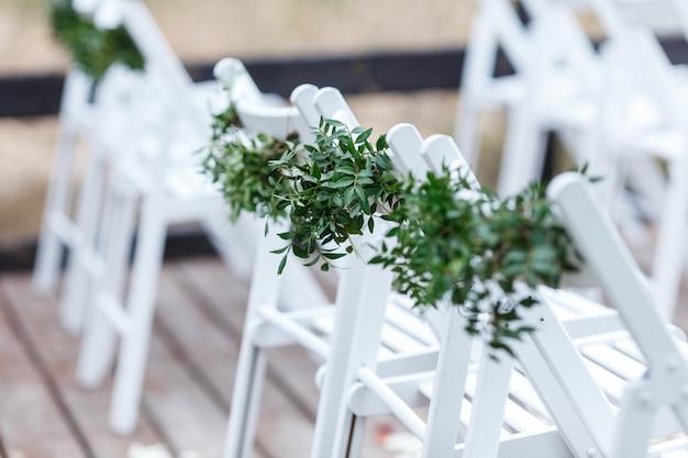 緑とユーカリで飾られた白い椅子は、桟橋での結婚式のゾーンにあります