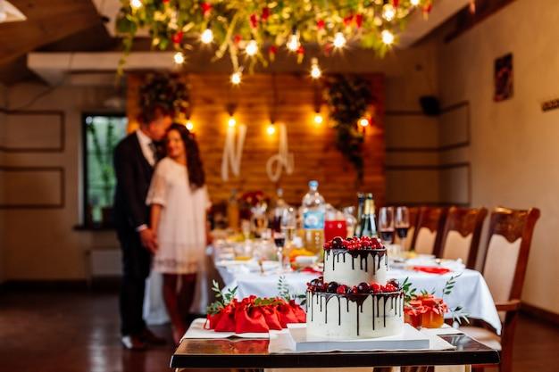 Двухуровневый белый свадебный торт, украшенный свежими красными фруктами и ягодами, залитый шоколадом