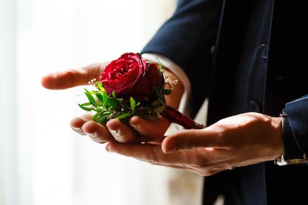 Молодой жених в темно-синем костюме держит в руках бутоньерку с красной розой