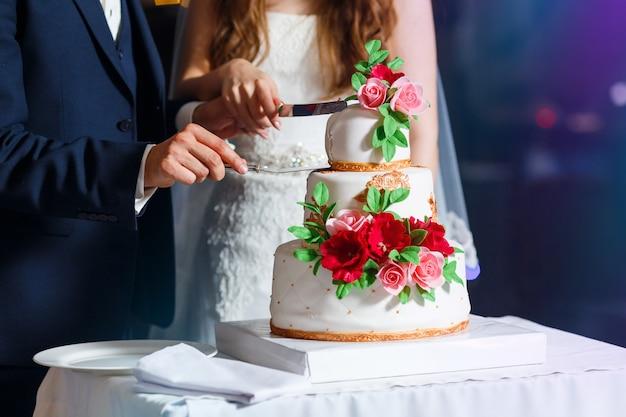 紺のスーツの新郎とドレスの花嫁は、美しいマルチレベルのウェディングケーキをカット