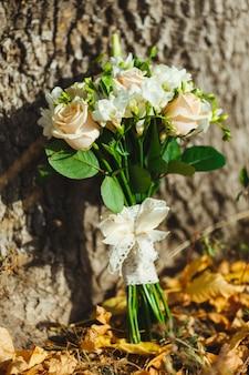 Красивый свадебный букет из роз лежащих на желтых осенних листьях