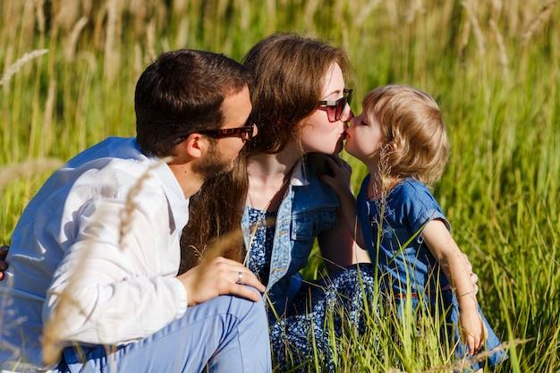 彼らの小さな娘にキスサングラスの若い親