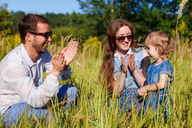 サングラスの若い親は、小さな笑顔の娘と彼らの手のひらをたたく