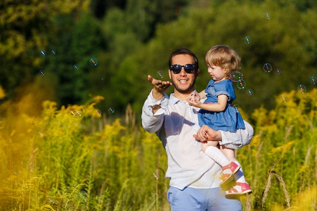 Молодой отец с маленькой дочкой пытается поймать мыльные пузыри