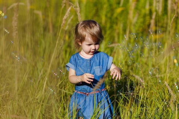 Маленькая девочка в голубом платье играет в парке летом