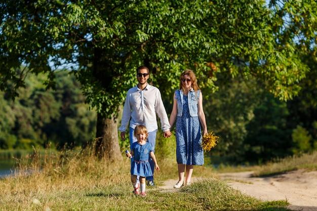 Молодые родители в солнечных очках и их маленькая дочь в парке
