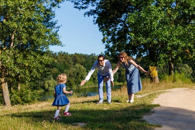 サングラスの若い親と公園で小さな娘