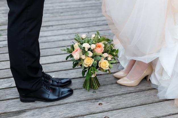 結婚式の詳細:新郎新婦のクラシックな黒とベージュの靴。それらの間の地面に立っているバラの花束。お互いの前に立つ新婚夫婦