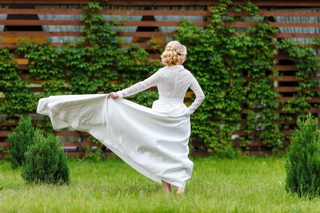 Молодая блондинка невеста в красивом белом платье с кружевной спиной, танцы на траве. вид сзади, лето, на улице