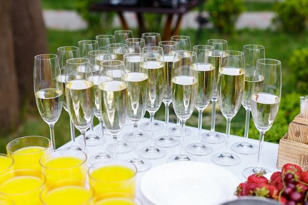 Наполненные бокалы с шампанским стоят рядами на столе. свадьба, питание на свежем воздухе. напитки, соки и фрукты - праздничный банкет, прием