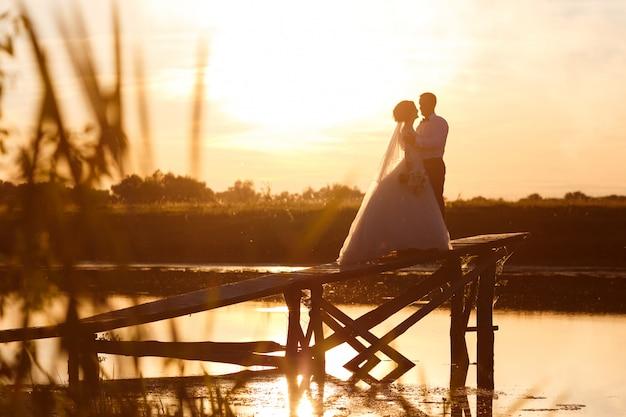Жених и невеста обнимаются стоя на мосту на закате. силуэты поцелуи молодоженов на фоне реки и неба. романтическая фотосессия для влюбленной пары
