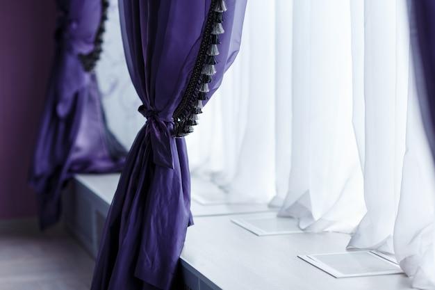 幅の広い窓に沿った紫のトレンディなカーテン