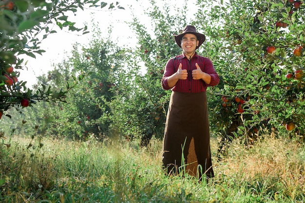 熟したリンゴを収集する庭で若い幸せな男