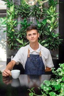 Официант зеленые белые листья кофейная чашка портрет молодой мужчина бариста обслуживание кофе клиент кафе фартук день св. патрика