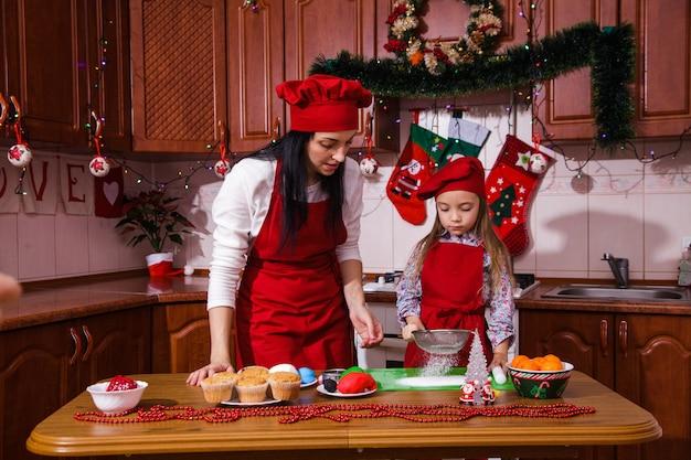 Рождественская вечеринка ужин меню десерт идея шоколад мята кексы сыр крем сахар посыпать украшения мать дочь новый год красный фартук шеф-повар главный кондитер