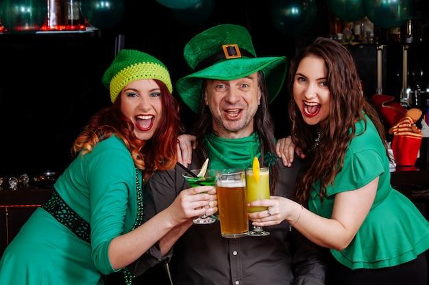 Молодые празднуют патрик день веселье бар карнавал головные уборы девушка мужчина пиво коктейль зеленая одежда шляпа улыбка красивый гном