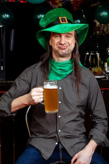 若いを祝うパトリックの日楽しいバーカーニバルヘッドギア女の子男ビールカクテル緑服帽子笑顔美しいレプラコーン