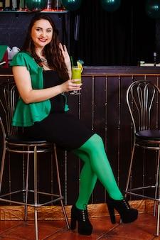 Молодые празднуют патрик день веселье бар карнавал головные уборы девушка мужчина пиво коктейль зеленая одежда шляпа улыбка красиво