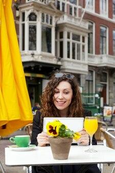 旅行ジュースオレンジイエローガールコート巻き毛タブレットヨーロッパコミュニケーションスマイルストリート古い家オランダハーグ花コーヒー太陽