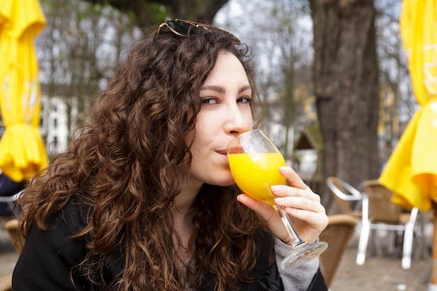フレッシュジュースを飲むオレンジ黄色の女の子コート巻き毛笑顔通りオランダハーグ太陽春ブルネット手持ち株ガラス