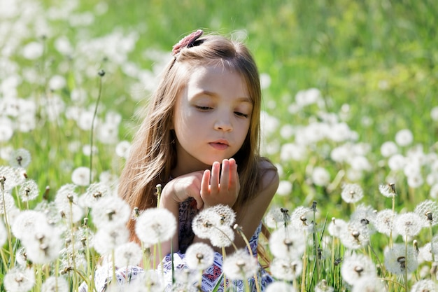 Маленькая девочка наслаждается одуванчиками на поле или зеленом луге весной солнечный день.