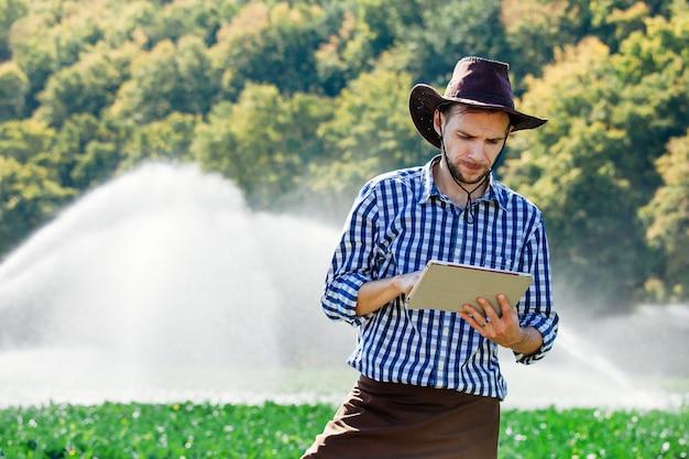 農夫の男性農学者が収穫を確認し、スプリンクラーシステムを備えたプランテーションにコンピューターの技術を使用しています。