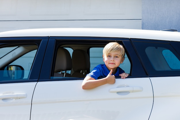 Забавный мальчик в машине с открытым окном и жестом ок
