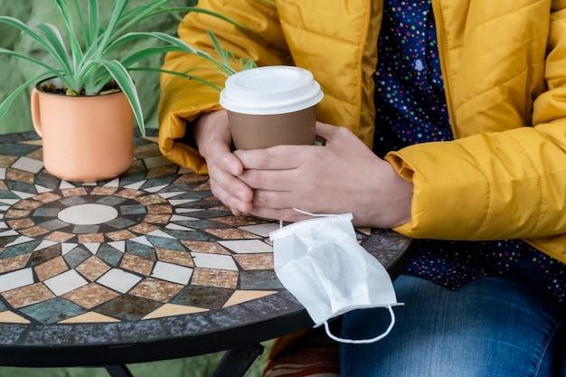 Женщина вручает медицинскую маску кофейный столик кофейной чашки, чтобы стать желтой