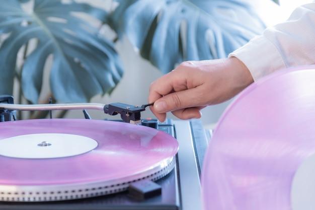 ビンテージレコードプレーヤーピンクビニールレコード手熱帯葉古いターンテーブル