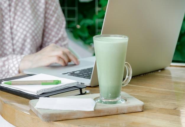 Женщина чашка зеленого маття латте кофе чай стекло рабочее место кафе терасса домашний фрилансер