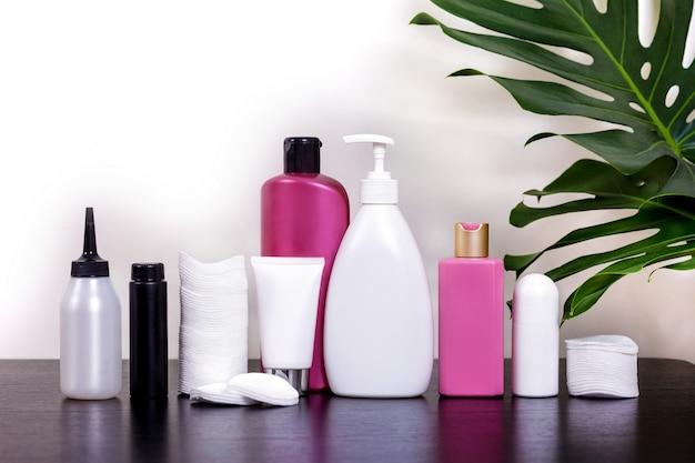熱帯の葉と黒いテーブルの白いチューブとバス用品の化粧品。